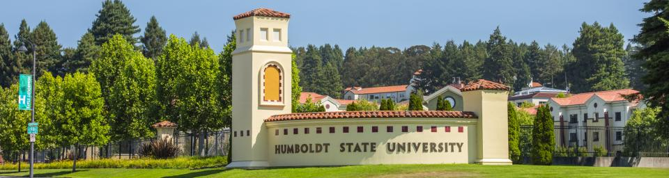 """sign  with buildings and trees in the background, reading """"Humboldt State University"""""""