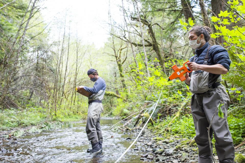 2 masked students standing in a creek gathering data