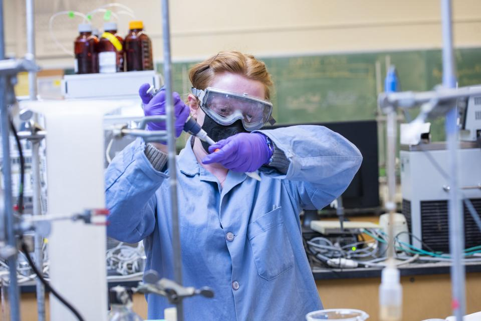student in ppe pipetting something in a lab