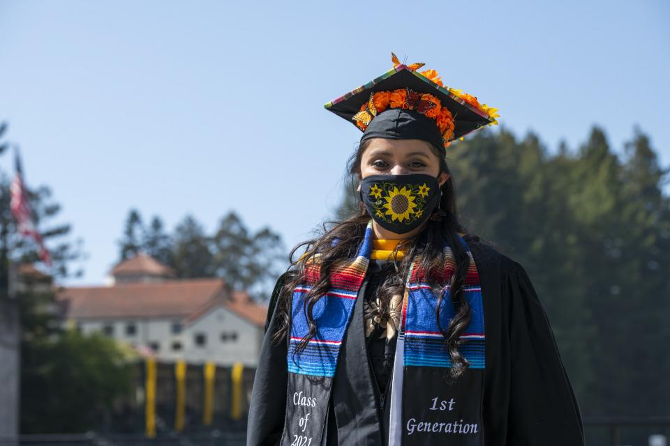graduate in sunflower mask, graduation robes, and a first generation sash